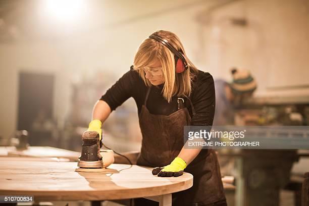 Woman using power sander