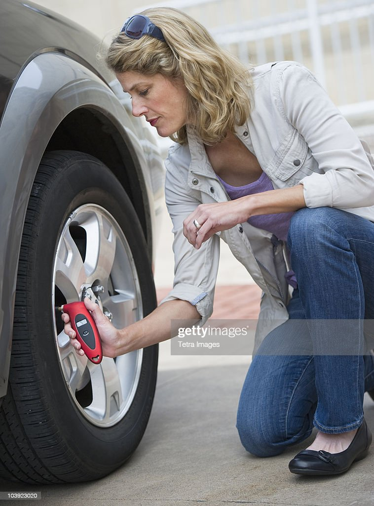 Woman using pressure gauge to check tire pressure