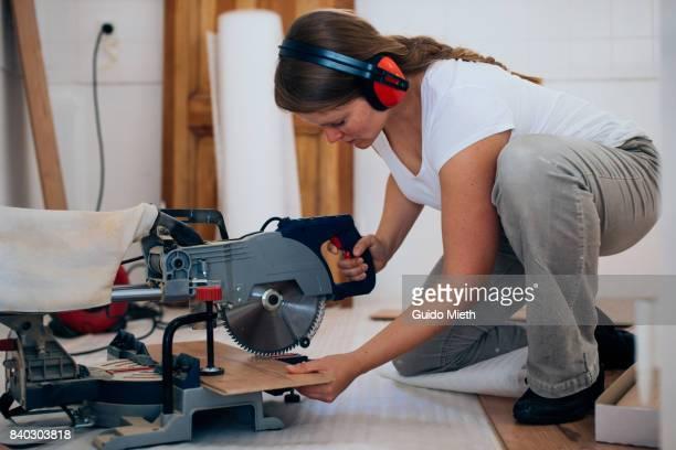 Woman using saw.