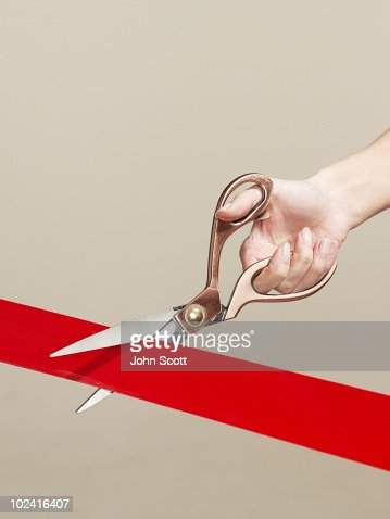 Woman using scissors to cut opening ribbon