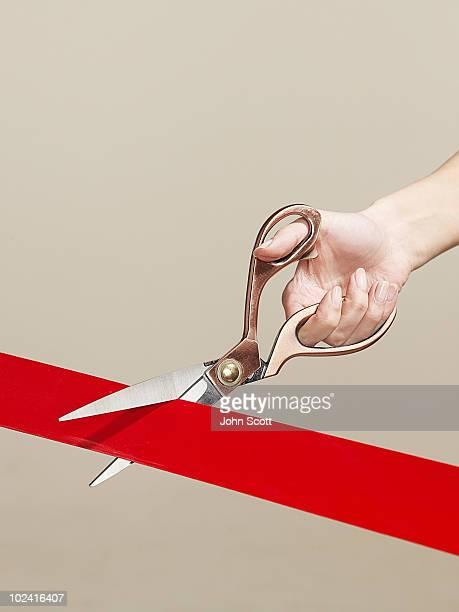 Woman using scissors to cut opening ribbon