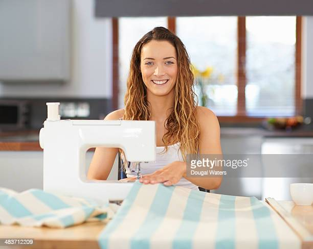 Woman using sewing machine at kitchen table.