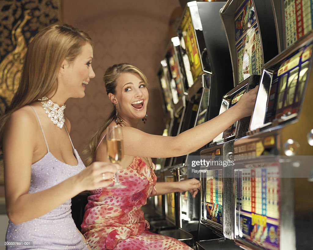 Woman using slot machine, smiling at friend holding champagne flute : Stock Photo