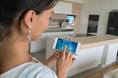 "Woman at home using smart home app on her cell phone -"" technology concepts. Design on screen was made from scratch by us"