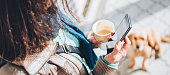 Woman using smart phone and holding coffee outdoor
