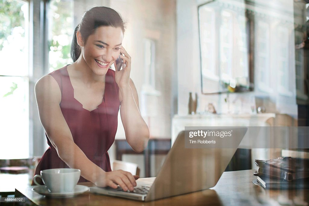 Woman using smart phone and laptop. : Stock Photo