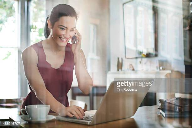 Woman using smart phone and laptop.