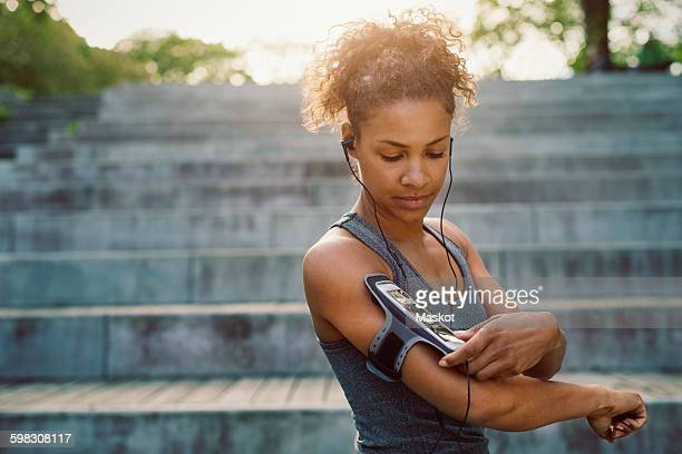 Woman using smart phone armband while exercising