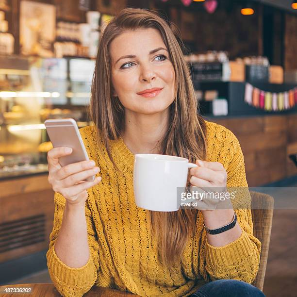 Woman using smart phone at coffee shop.