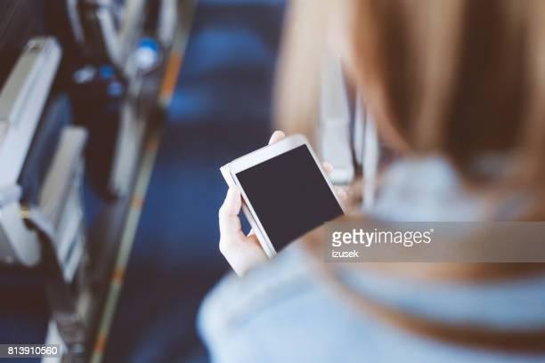 Vrouw met behulp van slimme telefoon tijdens vlucht