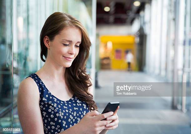 Woman using smart phone in glass area.
