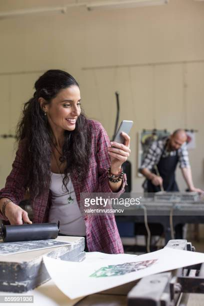 Woman using smart phone in printing house