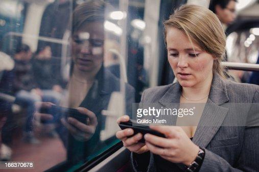 Woman using smart phone in subway.