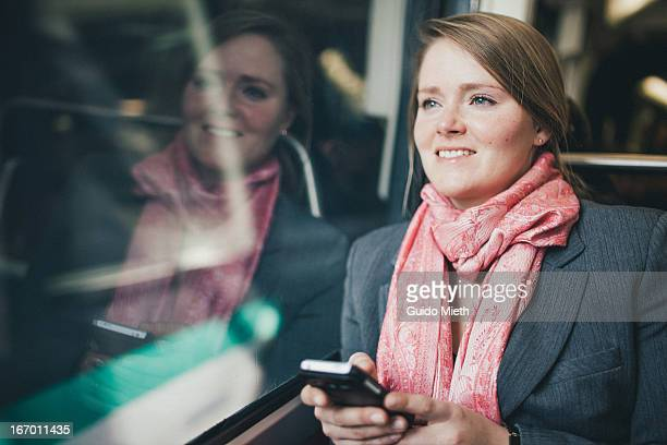 Woman using smart phone in subway.