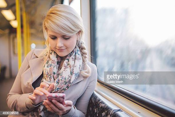Woman using smart phone in subway