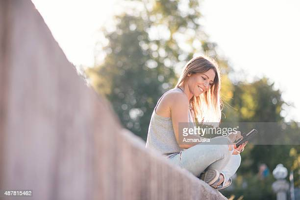Woman using smart phone in the park at sunset