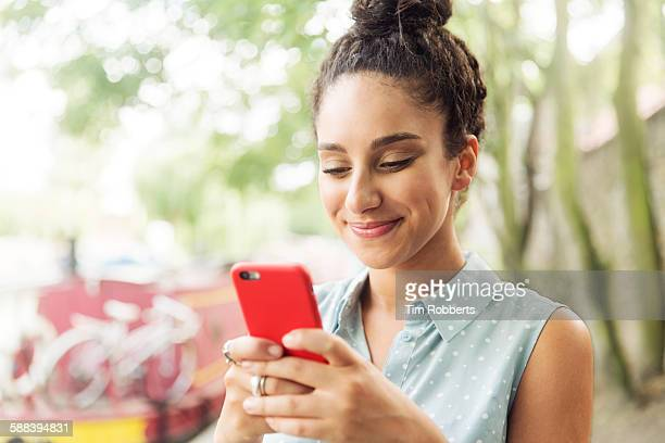 Woman using smart phone next to river.
