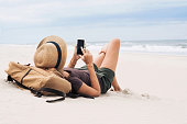 Resting woman using smart phone on a beach