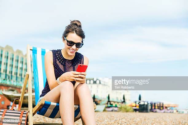 Woman using smart phone on deckchair.