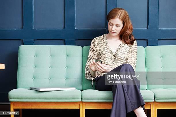 Woman using smart phone on sofa.