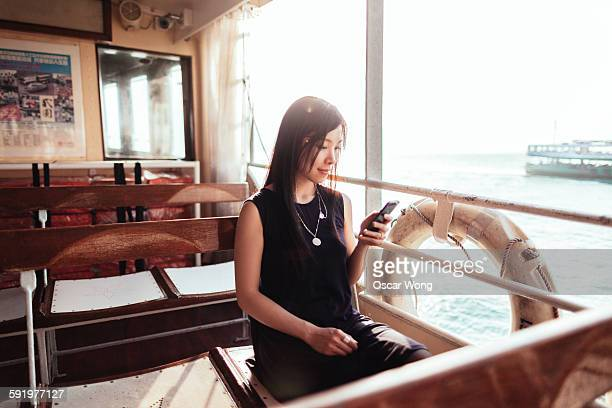 Woman using smart phone on the ferry