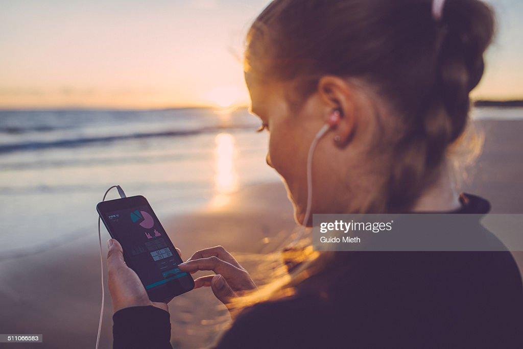 Woman using smart phone seaside.