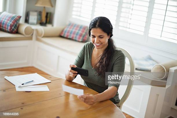 Woman Using Smart Phone To Deposit Check At Home