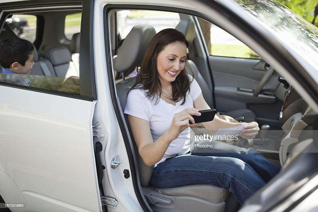 Woman Using Smart Phone To Deposit Check
