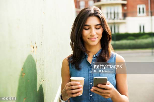 Woman using smart phone with coffee