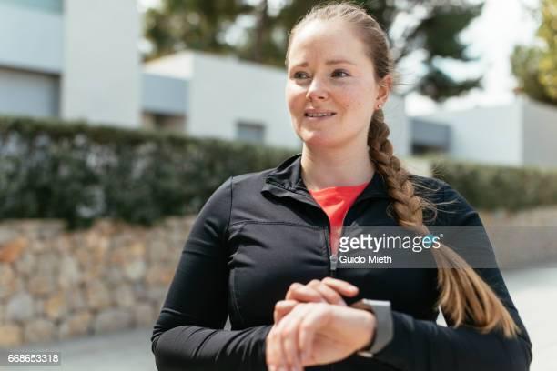 Woman using smart watch after running.