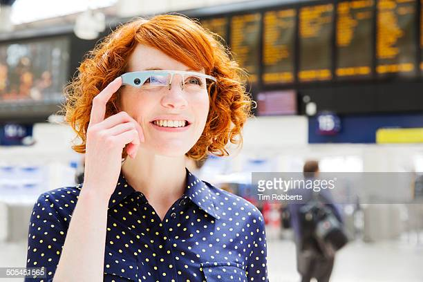 Woman using Smart-Glass at train station.