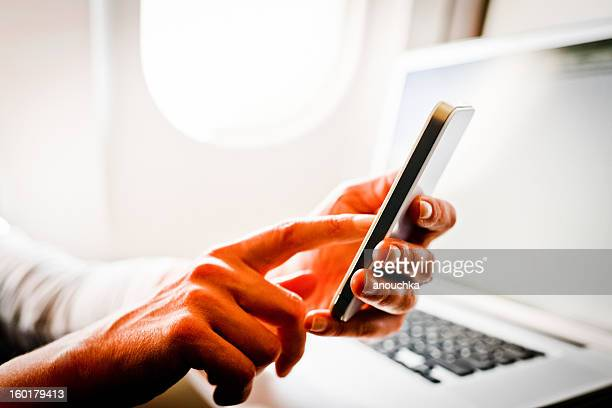Woman using smartphone and laptop in airplane during flight