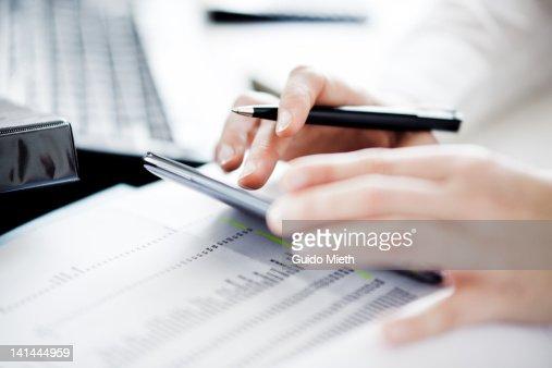 Woman using smartphone as calculator. : Stock Photo
