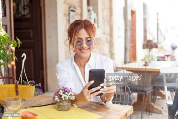 Woman using smartphone at cafe