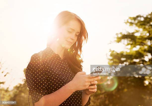 Woman using smartphone at sunset.