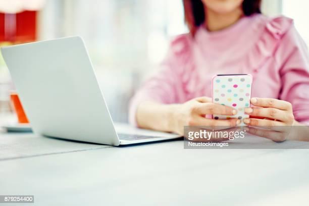 喫茶店のテーブルの上のノート パソコンでスマート フォンを使用しての女性