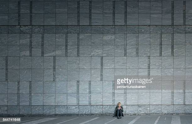 Woman using smartphone by large wall.