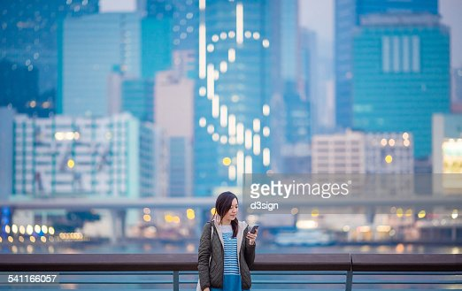 Woman using smartphone by the harbour in city