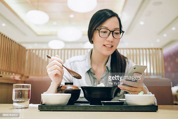 Woman using smartphone during meal in a restaurant