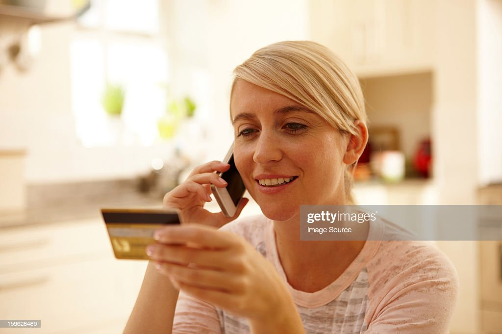 Woman using smartphone, holding credit card : Stock Photo