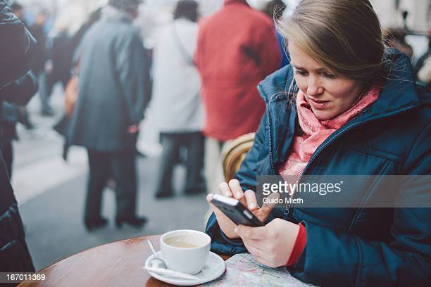 Woman using smartphone in coffee bar.