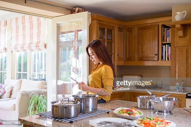 Woman Using Smartphone in Kitchen