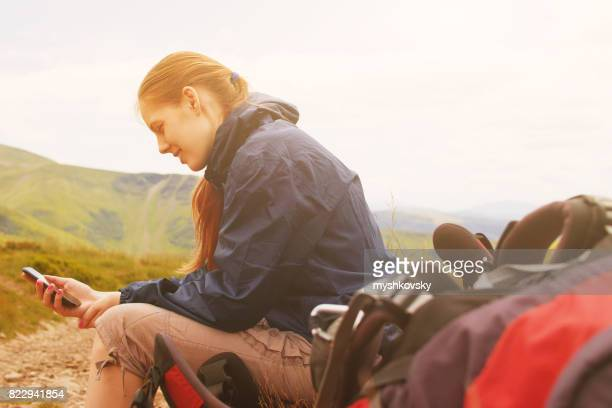 Woman using smartphone in mountains