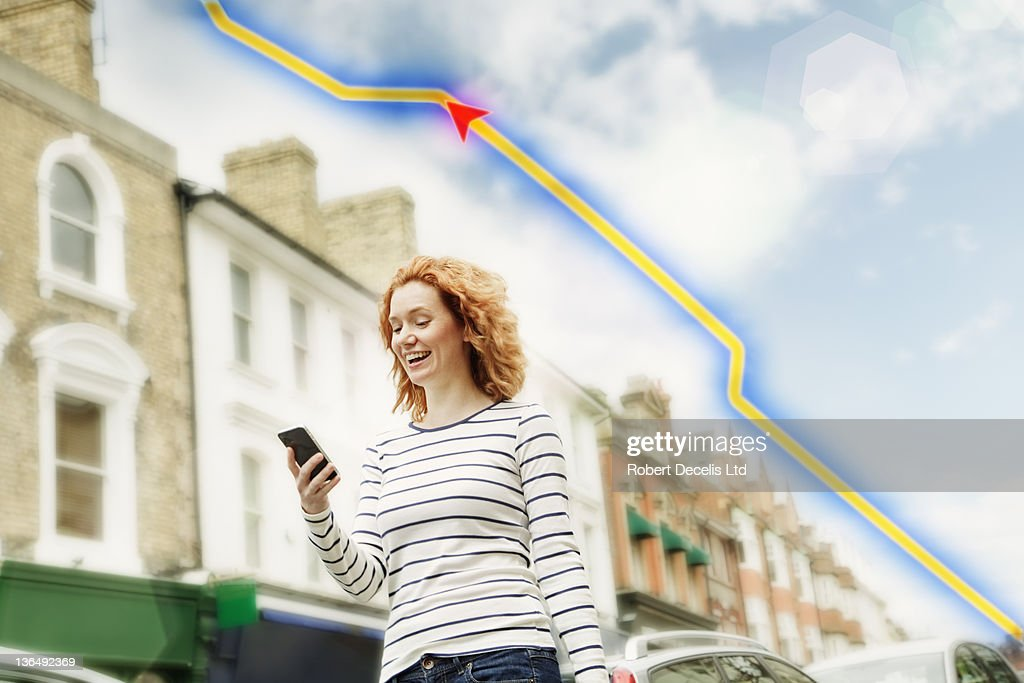 Woman using smartphone in street : Stock Photo