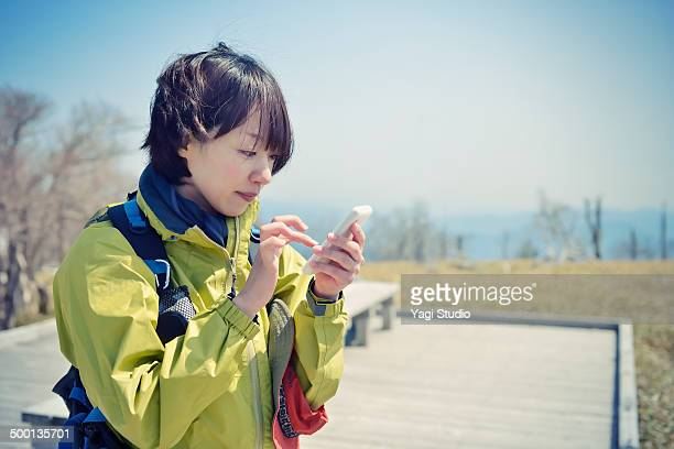 Woman using smartphone in the mountains