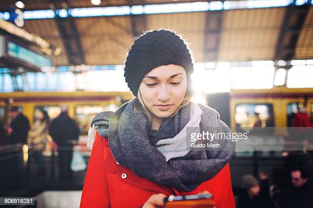 Woman using smartphone on a train station.