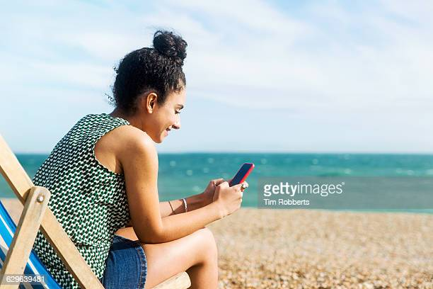 Woman using smartphone on beach.