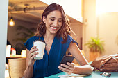 Young beautiful woman holding coffee paper cup and looking at smartphone while sitting at cafeteria. Happy university student using mobile phone. Businesswoman in casual clothes drinking coffee, smili