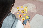 Close-up of woman using smartphone sending emojis. Social concept.