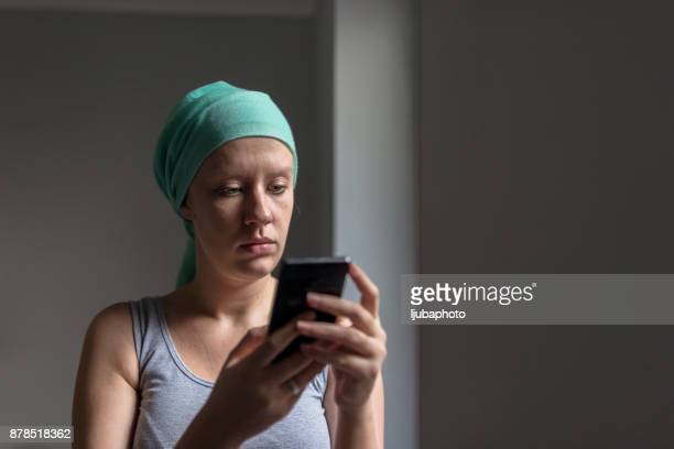 Woman using smartphone while fighting breast
